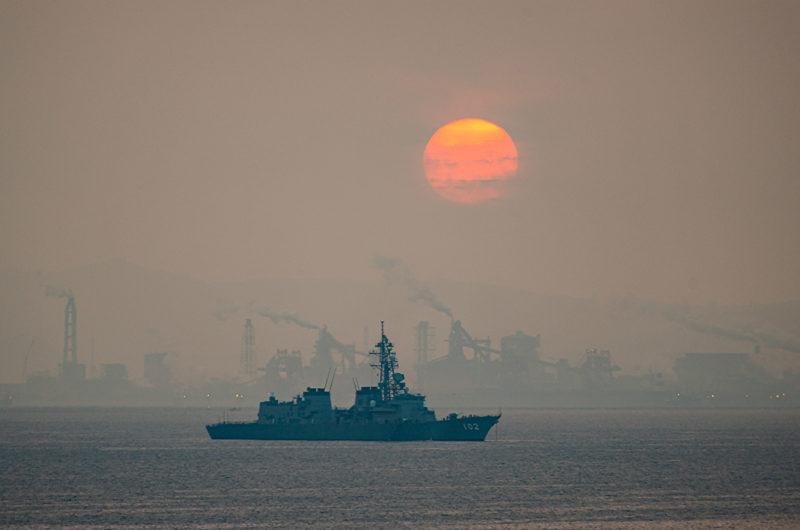 海岸沿いの工場地帯と朝日と海上自衛隊護衛艦